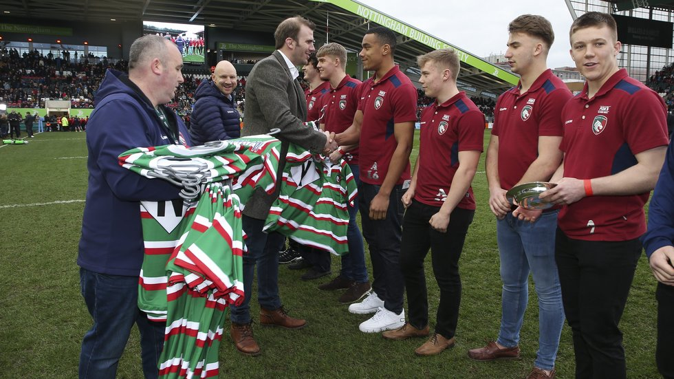 Tom Croft presents Tigers academy shirts on the pitch at half-time in the game against Wasps