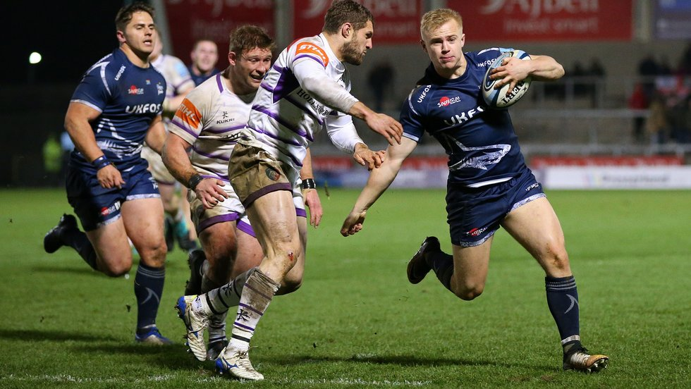 Jonah Holmes closes in to make a tackle on Sharks wing Arron Reed at the AJ Bell Stadium
