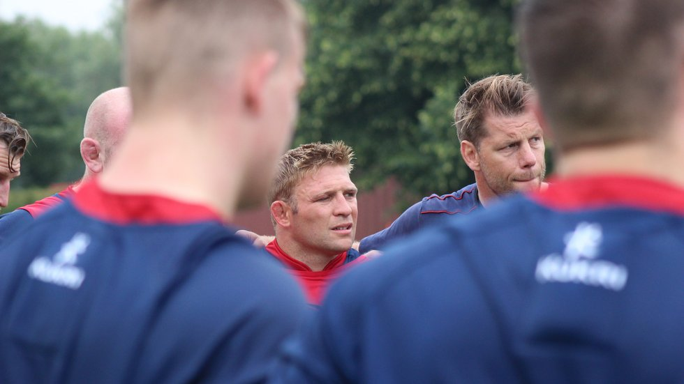 Tom Youngs and Brett Deacon listening in during a team huddle at the club's Oval Park Training Ground.