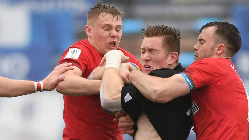 Sam Costelow (left) stands up to an All Blacks attack in the rain of Rosario