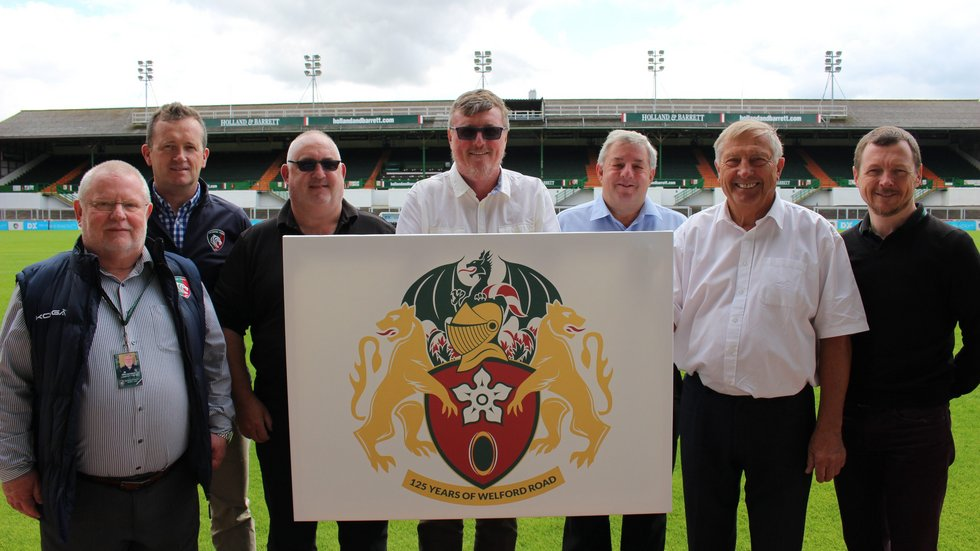 Eric Barker, Scott Clarke, Harvey Gardiner, Stuart Farmer, chief executive Simon Cohen, former club president Mike Harrison and Gary Sherrard pose with Tigers 125 crest