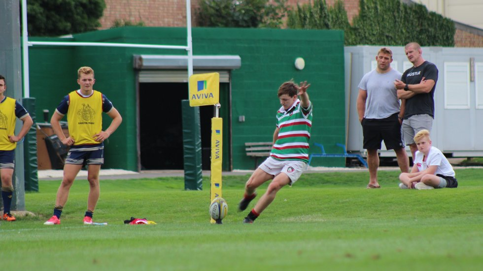 Charlie Titcombe attempts a conversion from the sideline at Oval Park, as club captain Tom Youngs and former Tigers Graham Rowntree watch on at Oval Park